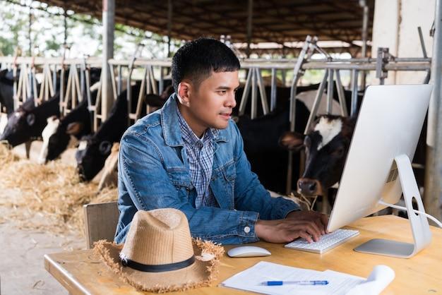 Farmer używa komputera do informacji o gospodarstwie. aby sprzedawać mleko online