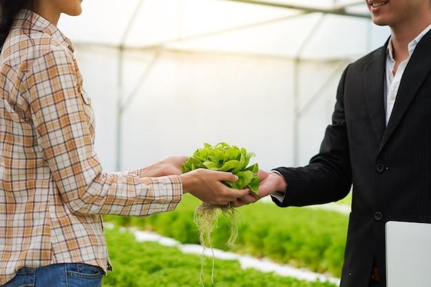 Farmer zajmuje się i zgadza z biznesmenem na dostarczanie i sprzedaż produktów rolnych