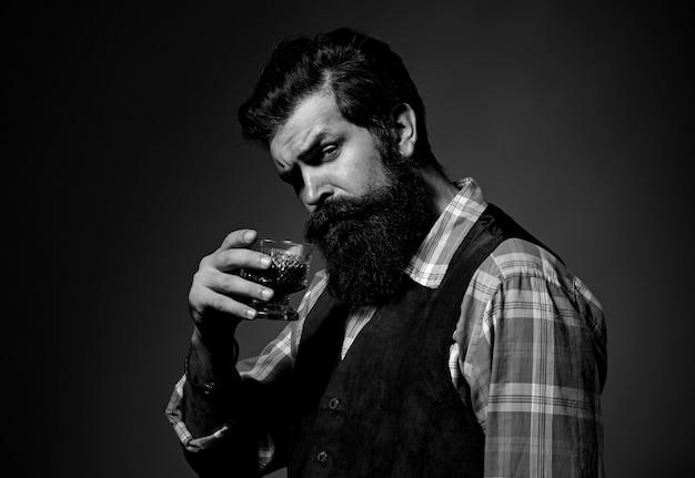 Fartuch skórzany barmana trzyma koktajl whisky w szkle. brodata whisky