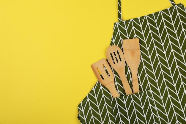 Fartuch z naczyniami na żółtym tle, miejsca na tekst.