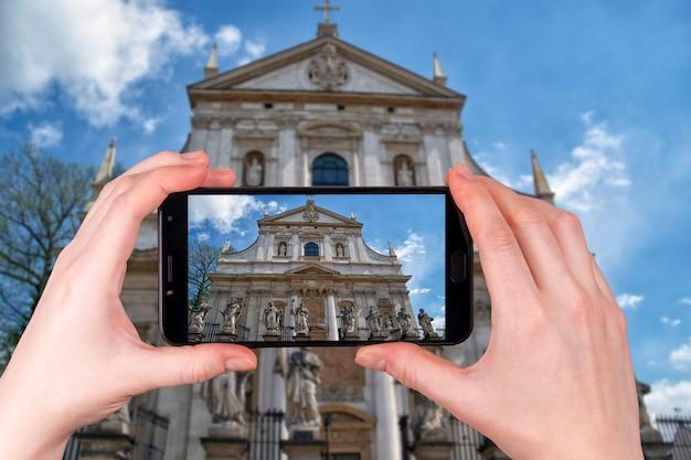 Fasada barokowego kościoła św. piotra i pawła w krakowie. polska. turysta robi zdjęcie