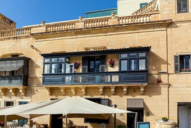 Fasada budynku mieszkalnego z tradycyjnym drewnianym balkonem w ciemnym kolorze na malcie.