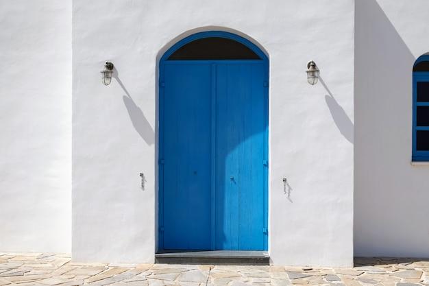 Fasada budynku z niebieskimi drzwiami.
