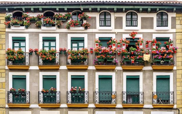 Fasada domu z balkonami pełnymi kwiatów w mieście hondarribia w kraju basków. hiszpania.