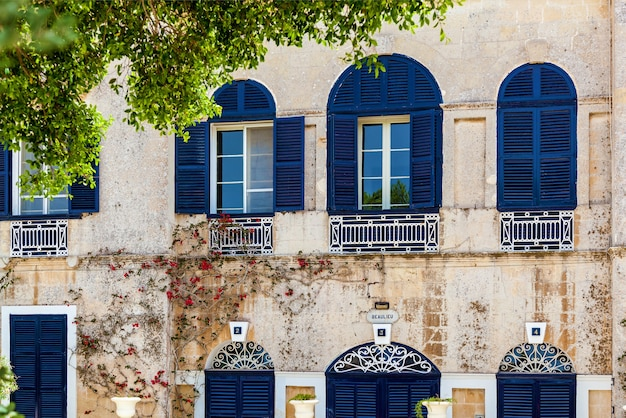 Fasada domu z niebieskimi drewnianymi oknami i drzwiami w mieście mdina na malcie. zabytki wyspy malta