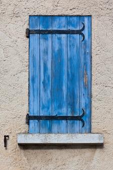 Fasada domu z niebieskimi okiennicami we francji
