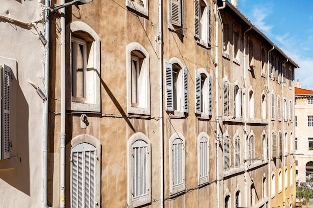 Fasada domu z okiennicami na starym mieście marsylii w jasny, słoneczny dzień.