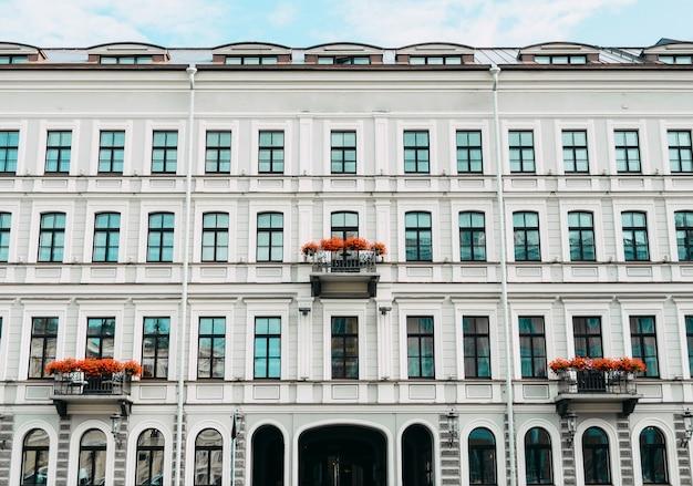 Fasada hotelu z oknami balkonami kwiatowymi.