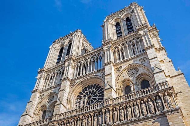 Fasada katedralny notre-dame de paris przeciw niebieskiemu niebu w paryż, francja