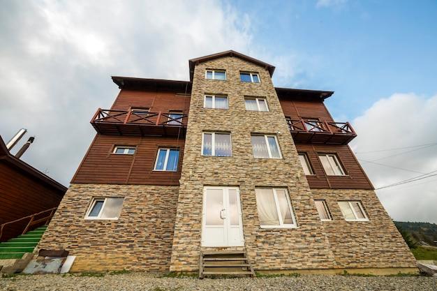 Fasada nowego drewnianego domku z materiałów drzewnych i kamienia z dekoracyjnym balkonem na niebieskim niebie.