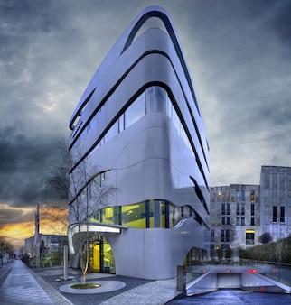 Fasada nowoczesnego budynku z geometrycznymi oknami i zakrzywionymi ścianami