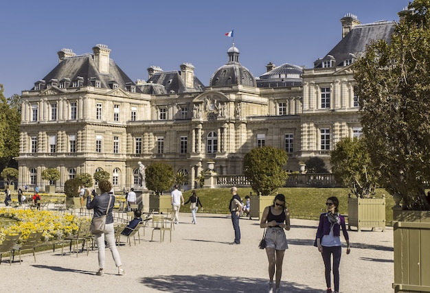 Fasada pałacu luksemburskiego w paryżu słoneczny dzień drzewo w wannie i stylowe dziewczyny francja
