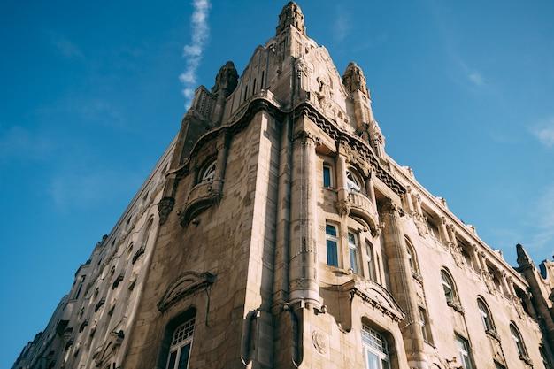 Fasada pięknego rogu starego budynku w budapeszcie przeciw błękitne niebo