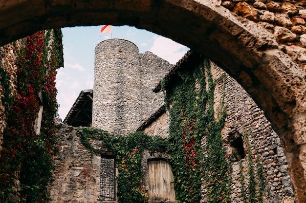 Fasada starych kamiennych budynków w perouges, czerwone okna, kwiaty, bluszcz, francja. wysokiej jakości zdjęcie