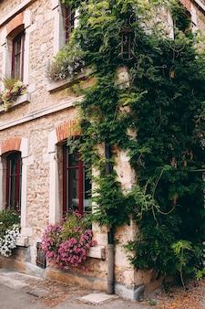 Fasada starych kamiennych budynków w perouges, czerwone okna, kwiaty, francja. wysokiej jakości zdjęcie