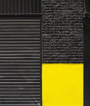 Fasada z cegły czarno-żółtej i roleta sklepowa