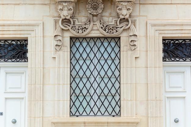 Fasada zabytkowego budynku z kamiennymi elementami dekoracyjnymi stare okno