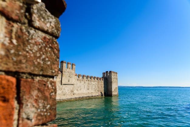 Fasada zamku sirmione otoczona wodą.