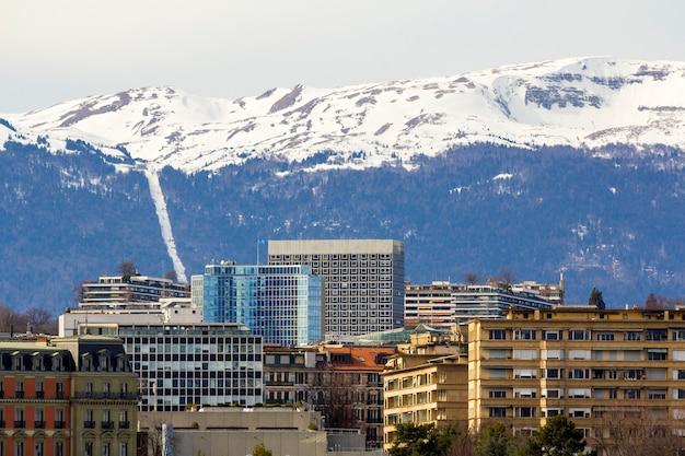 Fasady zabytkowych budynków w centrum genewy, szwajcaria na jeziorze leman ze śniegiem pokryte alpami szczyty w słoneczny dzień.