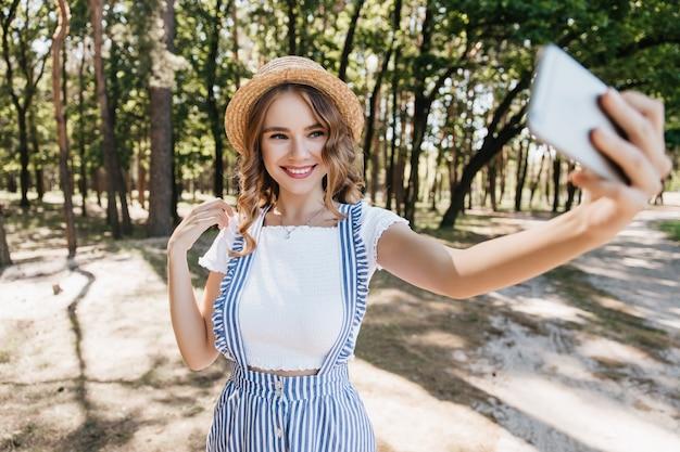 Fascynująca biała dziewczyna z falującymi włosami robi sobie zdjęcie w lesie. zewnątrz strzał śmiejąc się zadowolonej pani przy użyciu smartfona do selfie.