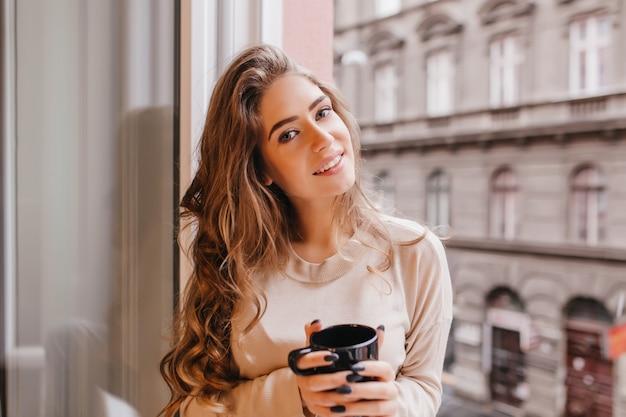 Fascynująca biała kobieta ubrana w beżową koszulę pozuje z romantycznym uśmiechem