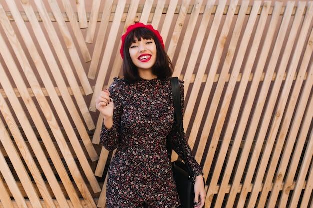 Fascynująca brunetka w modnym czerwonym berecie i sukience w stylu retro z kwiatowym nadrukiem, stojąca przed drewnianym płotem. urocza młoda kobieta z krótką fryzurą w francuski strój pozowanie na zewnątrz