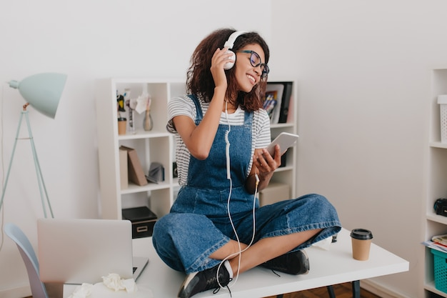 Fascynująca dziewczyna kręcone zabawy w miejscu pracy, trzymając w rękach smartfon