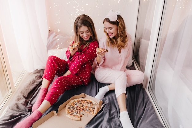 Fascynująca dziewczyna w czerwonym kombinezonie nocnym je pizzę w łóżku. dwie siostry w piżamie siedzą na czarnym prześcieradle.