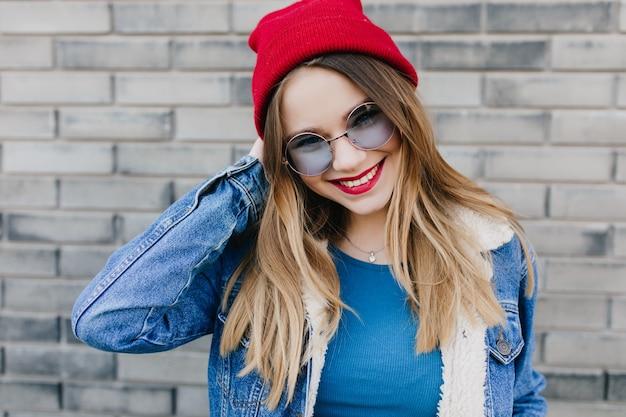 Fascynująca dziewczyna z zadowolonym wyrazem twarzy pozuje na ulicy rano. zewnętrzne zdjęcie przystojnej europejskiej pani nosi czerwony kapelusz i uśmiecha się