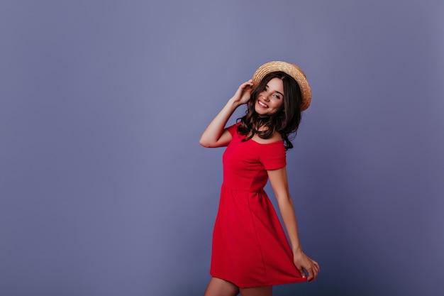 Fascynująca kaukaski dziewczyna tańczy i dotyka swojego letniego kapelusza. kryty portret uśmiechnięta piękna młoda kobieta w czerwonej sukience.
