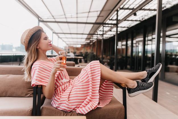 Fascynująca kaukaski dziewczyna w czarnych trampkach pozuje w kawiarni z lampką. portret sympatycznej blond modelki w kapeluszu, zabawy w restauracji.