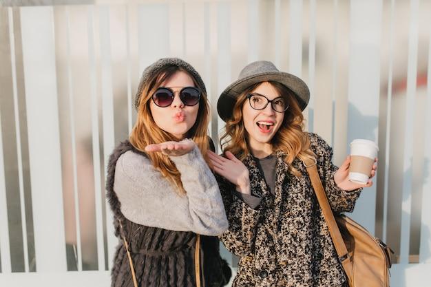 Fascynująca kobieta w eleganckim płaszczu i kapeluszu trzymająca filiżankę kawy, podczas gdy jej siostra pozuje z uroczym wyrazem twarzy. atrakcyjna młoda dama w stylowym swetrze wysyłająca pocałunek podczas spaceru z przyjacielem.