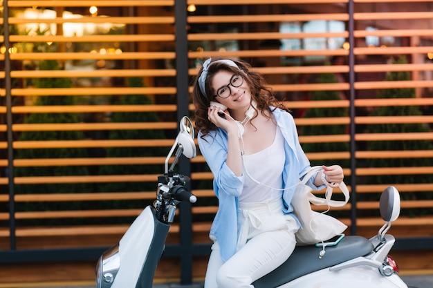 Fascynująca młoda dama w stylowych okularach trzymająca białą eko torbę i słuchająca muzyki w słuchawkach, odpoczywa po zakupach