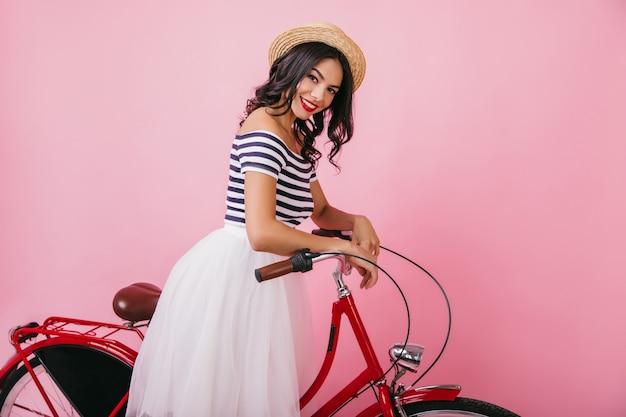 Fascynująca młoda dama z falowanymi włosami pozuje z czerwonym rowerem i się śmieje. kryty strzał uroczej kobiety łacińskiej w eleganckim słomkowym kapeluszu.