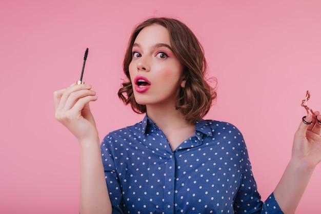 Fascynująca młoda kobieta w eleganckiej bluzce pozuje podczas robienia makijażu. ekstatyczna zaskoczona dziewczyna trzyma pędzel do tuszu do rzęs na różowej ścianie.