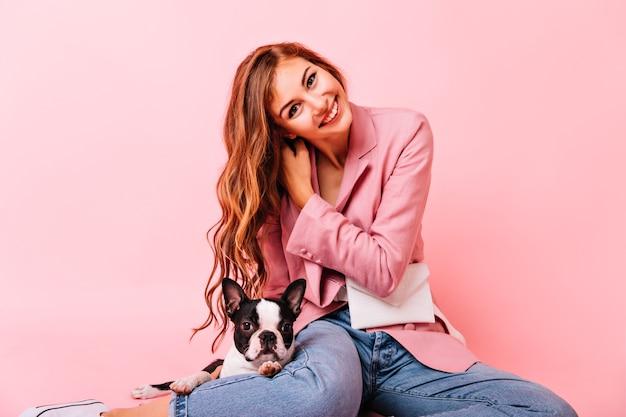 Fascynująca modelka bawiąca się długimi włosami podczas pozowania z psem. kryty portret zadowolony rudy pani siedzi na podłodze z buldoga francuskiego i uśmiecha się.