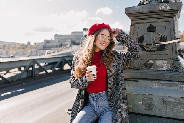 Fascynująca nieśmiała kobieta w okularach pije kawę na moście w wietrzny dzień