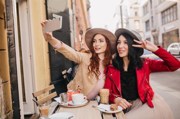 Fascynująca ruda kobieta robi selfie w kawiarni na świeżym powietrzu ze swoim przyjacielem
