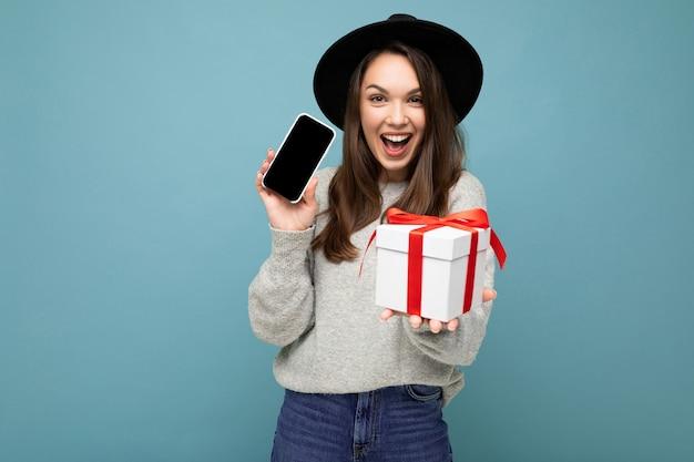 Fascynująca szczęśliwa radosna młoda brunetka kobieta na białym tle na niebieskim tle ściany stylowe