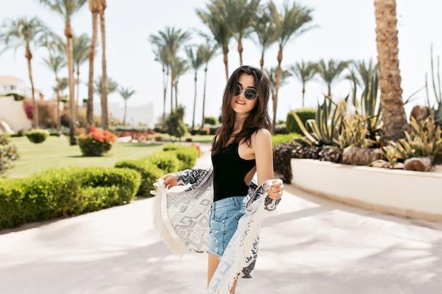 Fascynująca, zgrabna dziewczyna w szortach vintage tańczy na ulicy ciesząc się letnimi wakacjami. urocza młoda kobieta w okularach przeciwsłonecznych spędzająca czas w parku z palmami i pozująca z pięknym uśmiechem