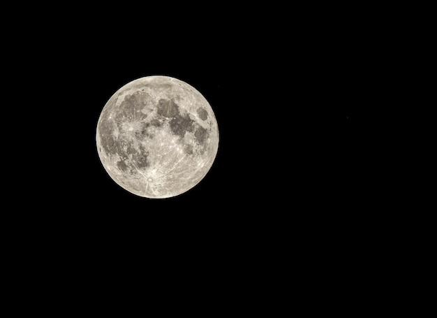 Fascynujący i piękny księżyc w pełni świecący w ciemności - doskonały do tapet