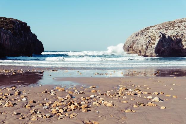 Fascynujący widok fal oceanu rozbijających się o skały w pogodny dzień