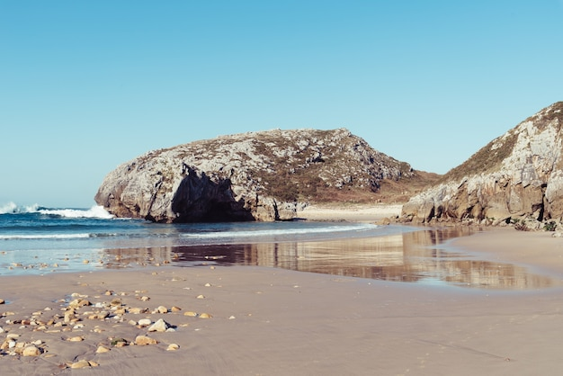 Fascynujący widok fal rozbijających się o skały w pobliżu brzegu w pogodny dzień