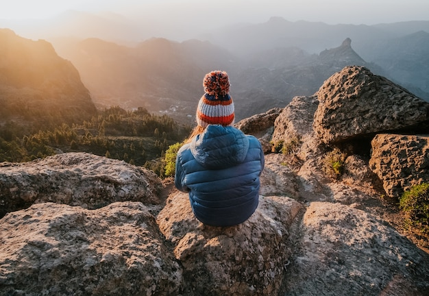 Fascynujący widok na góry skaliste ze szczytu i siedzącą tyłem kobietę