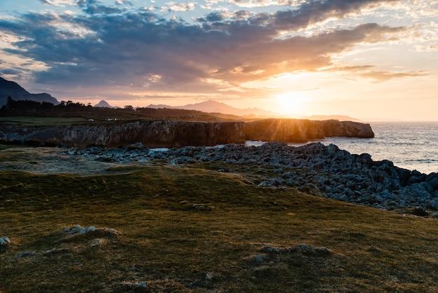 Fascynujący widok na plażę otoczoną górami skalistymi podczas zachodu słońca