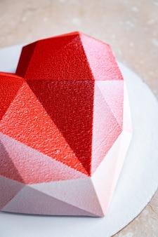 Fasetowany mus z czerwonego serca z welurową powłoką na stole z miękkiego różowego marmuru.