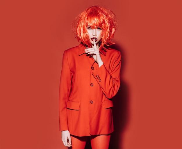 Fashion red concept pani patrząc na kamery z gestem ciszy dziewczyna w czerwonej kurtce formalnej czerwonej powierzchni