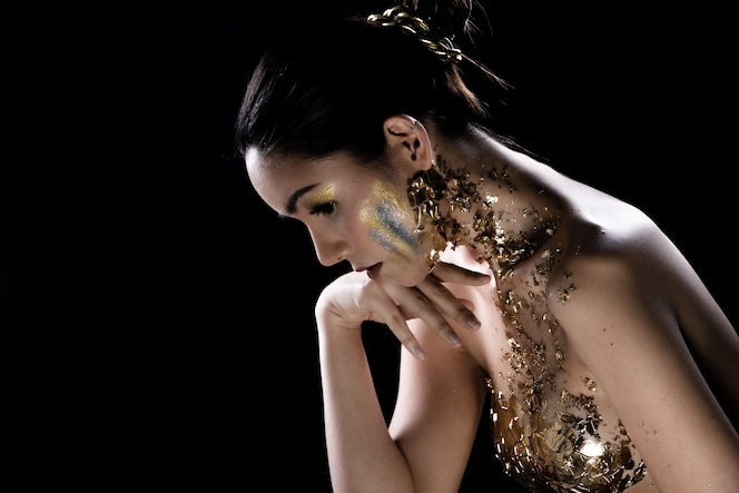 Fashion young asian woman oczy owinięte czarnymi włosami piękny makijaż ozdobiony złotą folią lub złotym liściem na całej klatce piersiowej. oświetlenie studyjne ciemne tło
