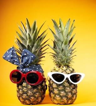 Fashionista w okularach przeciwsłonecznych na żółtym tle. dwa ananasy w szklankach