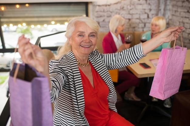 Fashionistka. starsza kobieta z torbami na zakupy wygląda na szczęśliwą